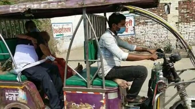 Due to non-availability of ambulance, someone is carrying the dead body on a bike by rickshaw.